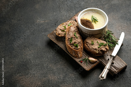 Fresh homemade chicken liver pate in ceramic bowl or ramekin and baguette slices with herbs and garlic on a dark background Wallpaper Mural