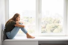 Sad Depressed Young Woman Having Social Problems Sitting On Windowsill
