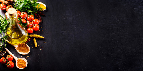 Food background. Top view of olive oil, cherry tomato, herbs and spices on rustic black slate. Colorful food ingredients border.