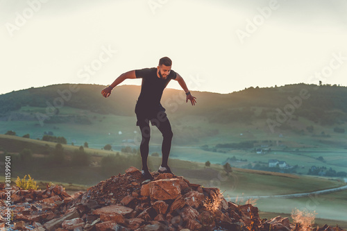 Fototapeta a man trains on a mountain in the early morning obraz