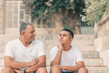 Teenager Son And Senior Father Sitting On Stairs And Talking. Two Generation.