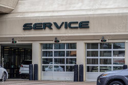Canvastavla White cars entering an automobile service center garage through an open garage door