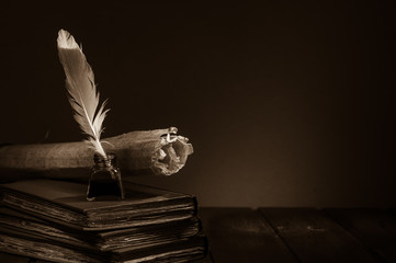 Quill pen and rolled papyrus sheets on a wooden table with old books, sepia effect