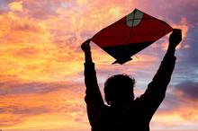 Boy Holding A Kite Above Head At Dusk