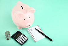 Pink Piggy Bank With Coins, Calculator And Notepad On Mint Background