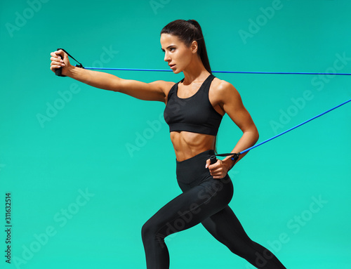 Foto Strong woman using resistance band in her exercise routine