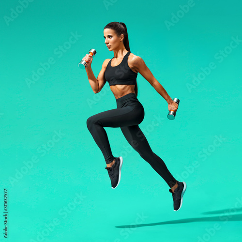 Sporty woman jumping with dumbbells Canvas Print