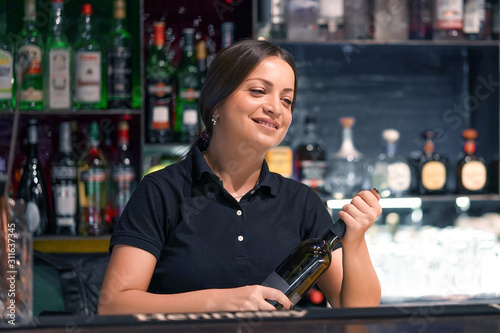 Portrain of caucasian bartender woman smiles and opens a bottle of red wine for the client of the hotel bar Wallpaper Mural