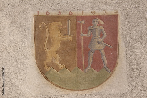 A historical mural depicting a lion and a warrior with a sword and an axe (1636-1937) on a wall in old city in Bludenz, Vorarlberg, Austria Canvas-taulu