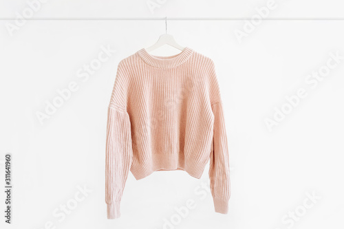Photo Feminine pale pink warm sweater on hanger on white background
