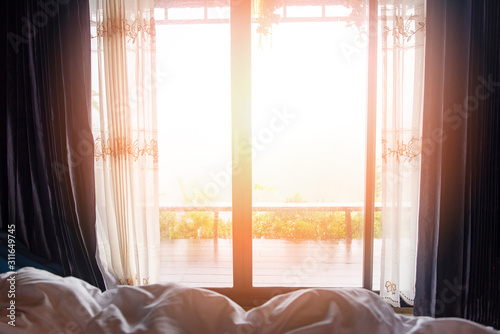 Obraz window view nature green mountain in the bed at bedroom morning and sunlight - window glass with drapery - fototapety do salonu