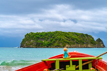 Toy Doll Sitting In Front Colorful Old Wooden Fishing Boat Docked By Water On Beautiful Beach Coast Sea Shore Landscape On Tropical Caribbean Island. Holiday Weekend Summer Vacation Setting In Jamaica