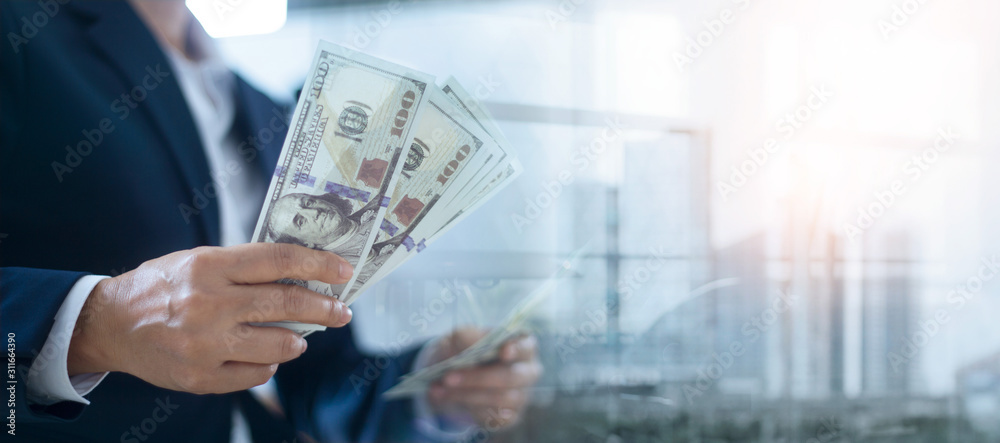 Obraz Businessman holding banknote in hands and analysis of investment on city background, Banking, Financial and investment. fototapeta, plakat