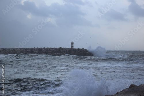 Fototapety, obrazy: Clashing wave with lighthouse in the background