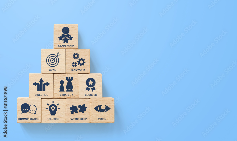 Fototapeta Wooden block stacking pyramid with icon leader business on blue background. Key success factors for leadership elements concept