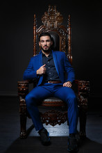 Elegant Man In A Classic Blue Suit Sitting In A Carved Wooden Chair Against A Dark Background.