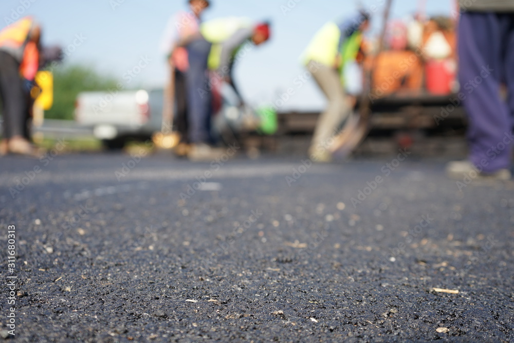 Fototapeta Construction workers on the asphalt road, blurred pictures