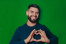 Sexy Man In Sweater Shows Heart With Fingers On The Green Background. Saint Valentine's Card With Copy Space.