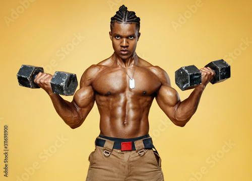 Handsome man doing exercise with dumbbells. Photo of muscular man on yellow background. Strength and motivation