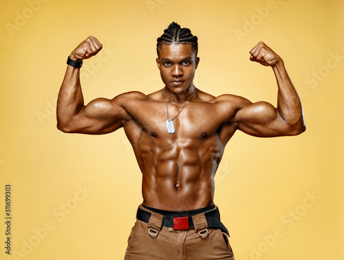 Athletic man posing. Photo of man with perfect physique on yellow background....