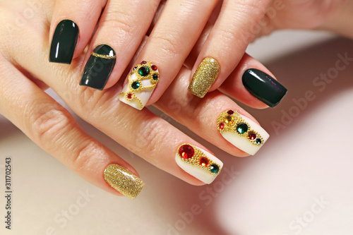 Fotografiet New year's fashionable beautiful festive manicure on short square nails with green lacquer color, with Golden sequins, bouillon and rhinestones of different colors