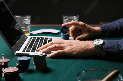 Fotografía Mature businessman playing poker online, closeup