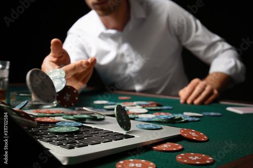 Fotomural Young man playing poker online, closeup