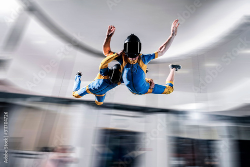 Fototapety, obrazy: Hobbies. Free people prefere active sports. Bird men conquers sky. Flying people in blue and yellow suit. Extreme as a hobby.