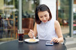 Asian woman using smartphone in coffee shop cafe