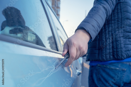 Photo Bad guy scratching the car door with a screwdriver in the parking lot on the street