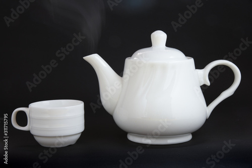 Fototapeta Hot tea in white ceramic teapot and cup with steam isolated on black background