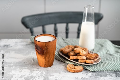 A wooden glass with milk on the kitchen table near to cookies Canvas Print