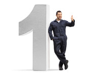 Handyman Leaning On A Big Number One And Gesturing A Thumb Up Sign