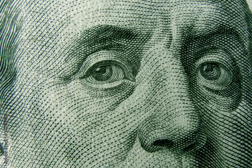 Fototapeta Closeup on Benjamin Franklin eyes from 100 dollar bill. American currency as a world money concept. obraz