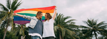 Two Women With Rainbow Flag On The Beach On A Background Of Palm Trees