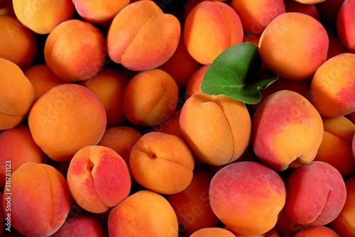 Heap of fresh apricots with one green leaf, closeup detail photo from above Fotobehang