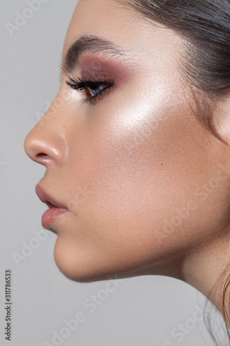 Slika na platnu Profile photo of a beautiful girl with professional makeup, ideal skin, rose eyeshadows and nude lips