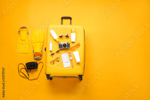 Suitcase with travel accessories on color background