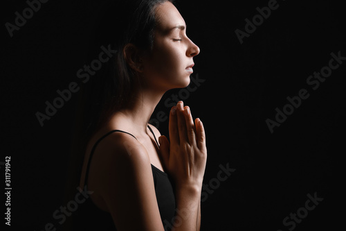 Photo Silhouette of praying young woman on dark background