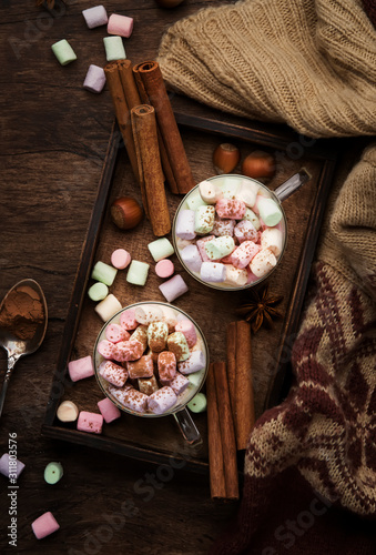 Hot winter or autumn drink with cocoa, white chocolate, spices and colorful marshmallows in cups on vintage wooden background with knitted warm sweater, top view with copy space