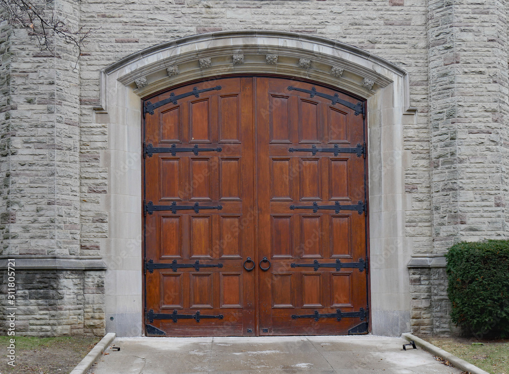 Obraz Large wood panelled gate in wall of stone building fototapeta, plakat