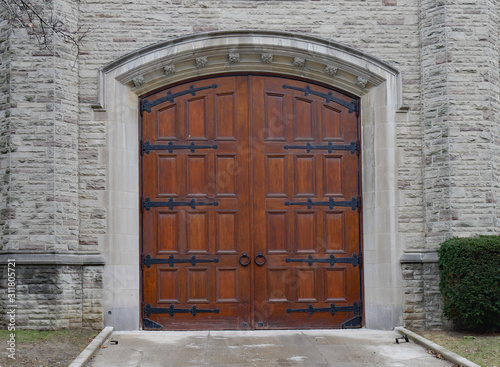 Fototapeta Large wood panelled gate in wall of stone building obraz