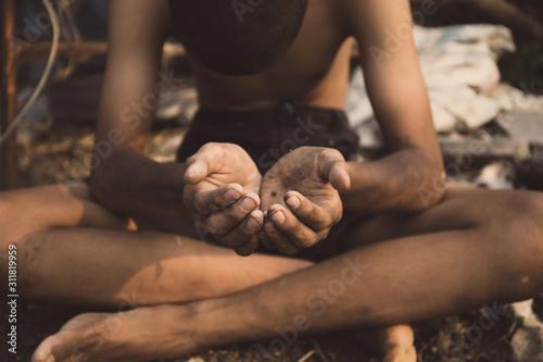 Fényképezés  poor child or beggar begging you for help sitting at dirty slum