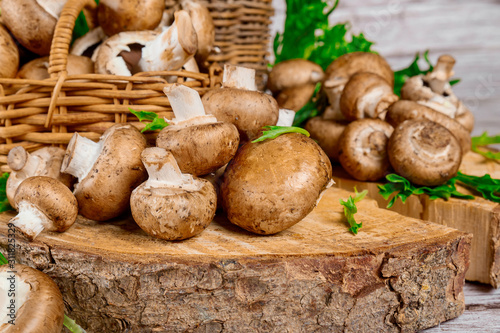 Brown mushrooms in wooden wicker baskets on wooden background.