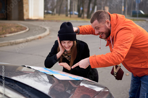 Young people argue near a car with a map on the road. Canvas Print