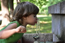 Child Drinks Water From A Foun...