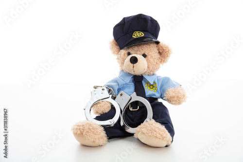 Fotografía  Cute teddy in policeman uniform and handcuffs isolated against white background
