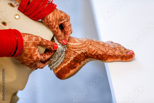Indian bridal putting anklets in leg Wallpaper Mural