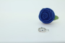 White Gold Diamond Ring On Blue Rose Setting On The White Background For Copy Space Photo