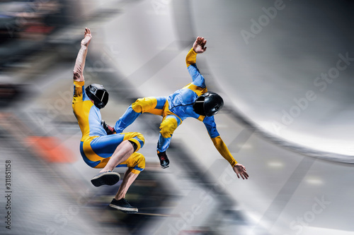 Fototapety, obrazy: Up. Extreme people prefere sky sport. Fly men perfoms trick in air. Parachutist in blue and yellow suit is in free fall. Skydiving is sport without rules.